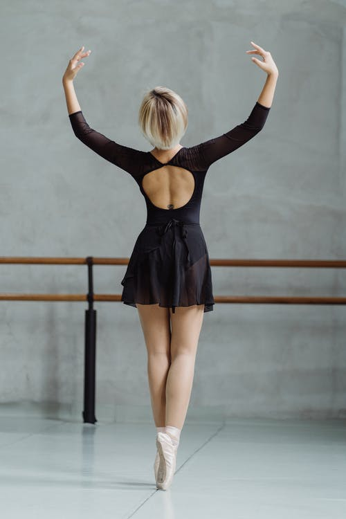 Faceless graceful ballerina standing on tiptoes with arms raised