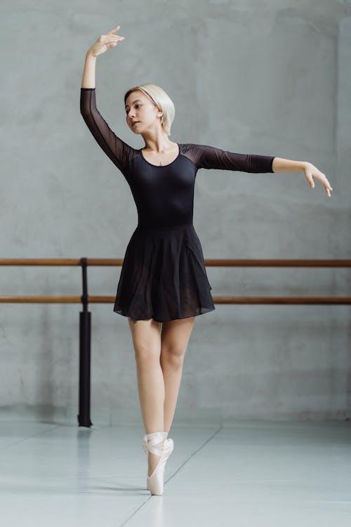 Gorgeous Asian ballerina performing dance in studio