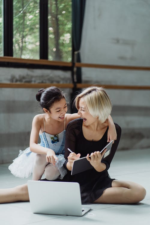Cheerful Asian woman and girl ballerinas using laptop on floor