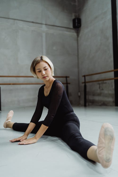Full body agile Asian ballerina in leotard sitting on floor and stretching legs while warming up before rehearsal