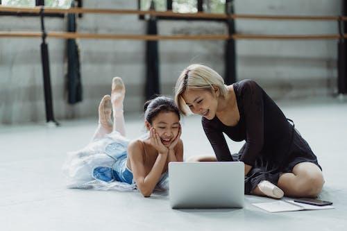 Full body of positive Asian female ballet instructor watching netbook sitting near girl in tutu skirt