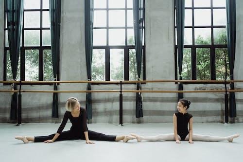 Flexible Fröhliche Ethnische Ballerinas, Die Sich Zusammen Erstrecken