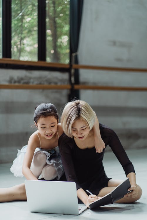 Smiling Asian ballerina sitting near coach taking notes and using laptop in dance hall