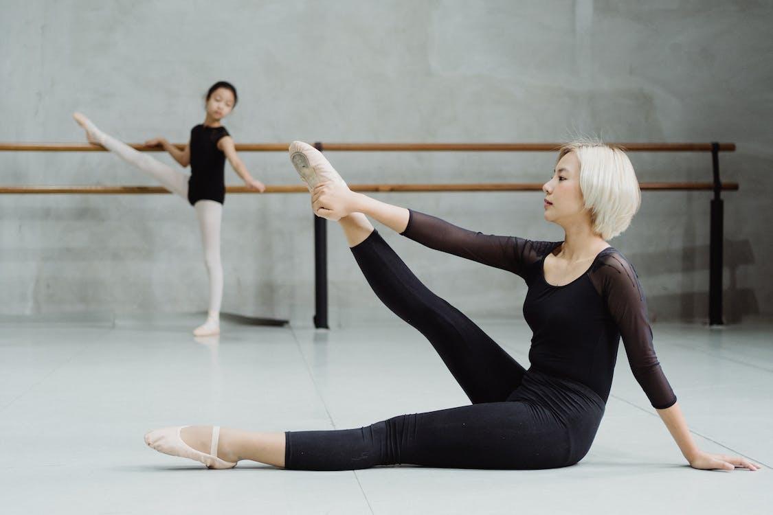Ethnic girl practicing ballet with tutor in studio