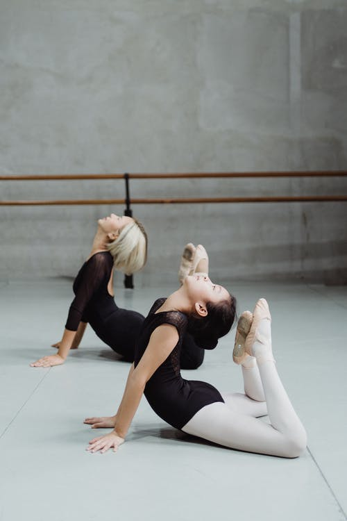 Flexible Asian ballerinas stretching on floor in dance class
