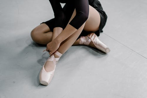 From above of crop anonymous female ballet dancer in pointe shoes sitting on floor in dance studio