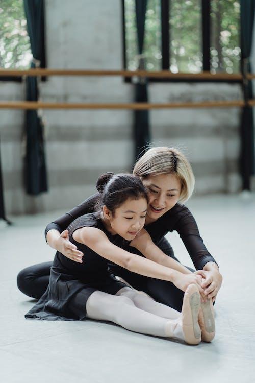 Full body positive Asian female ballet instructor sitting on floor and helping ballerina girl to stretch body in modern ballet school