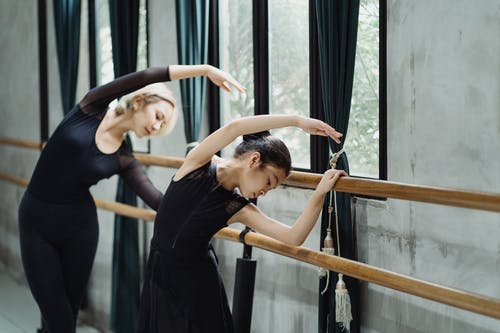 Flexible Asian female ballet instructor and girl trainee standing near barre with arms raised gracefully and bending to side during ballet class in light studio