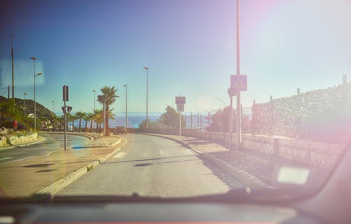 This picture is taken from inside a car through the windhield with the dashboard visible on the lower edge of the picture. The car is driving down a palm-lined ocean road under a blue sky with the ocean inthe background. The sunshine is reflected in the windshield of the car.