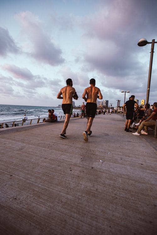 Full body back view of anonymous shirtless sportsmen jogging on paved waterfront near waving sea against cloudy sky during fitness training