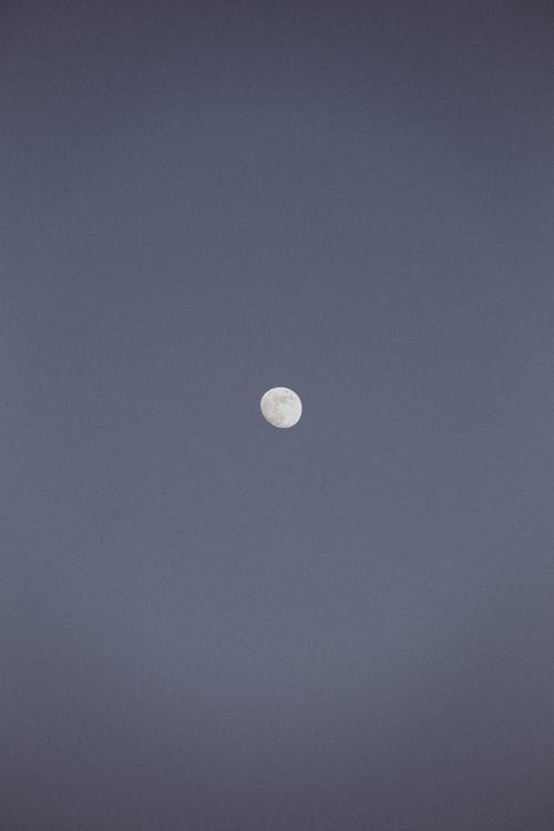 White full moon shining in distance on cloudless dark sky at sunset time in nature on evening time in atmosphere