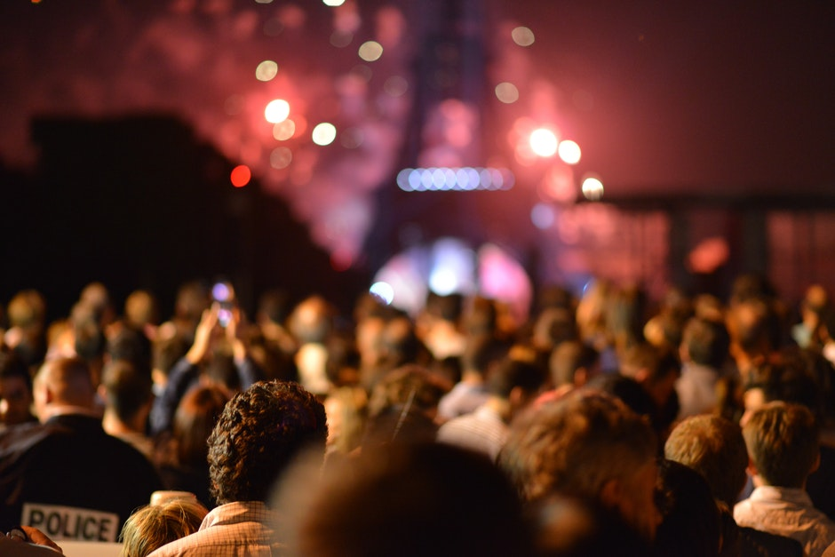 This photo displays a crowd of people who stand in front of the Eiffel Tower and who are watching the red colors of fireworks which seems to be happening behind and around the Eiffel Tower. On the lower left side a policeman is visible.
