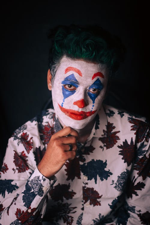 Pensive male in shirt with floral print with green hair and greasepaint on face touching chin and looking at camera on dark background