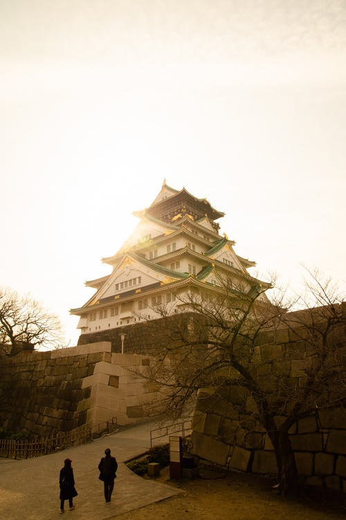 Exterior of Osaka Castle in authentic oriental style located on stone platforms in bright sunlight on early spring day