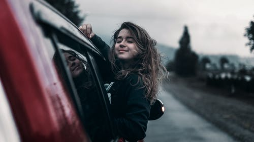 Young female leaning out of car window