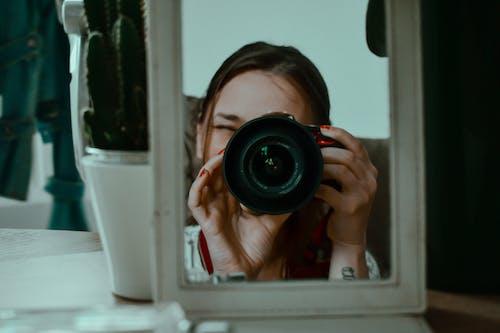 Woman taking photo through small mirror