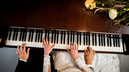 Woman in White Lace Wedding Dress Playing Piano