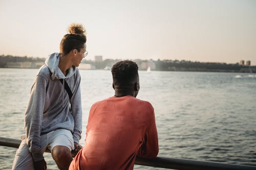 Young multiracial male friends in casual clothes standing on city waterfront and having conversation in early evening