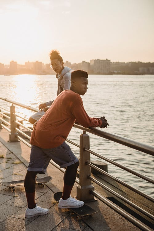 Multiethnic male skaters with skateboards standing near embankment handrail