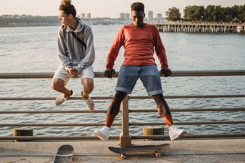 Sporty male skaters sitting on embankment railing in evening