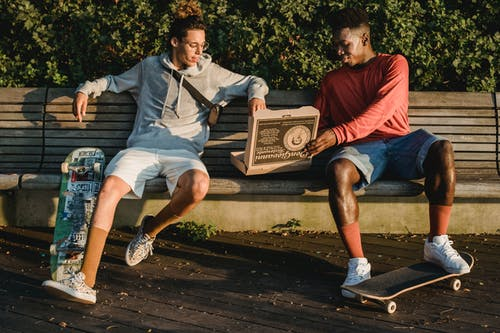 Full body content multiracial male friends with skateboards wearing casual shorts sitting on wooden bench and enjoying tasty fresh pizza in park