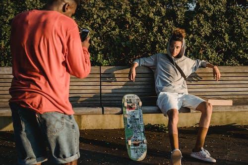 Black man taking photo of male skater sitting on bench