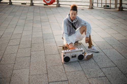 Content ethnic man sitting on skateboard with tape recorder