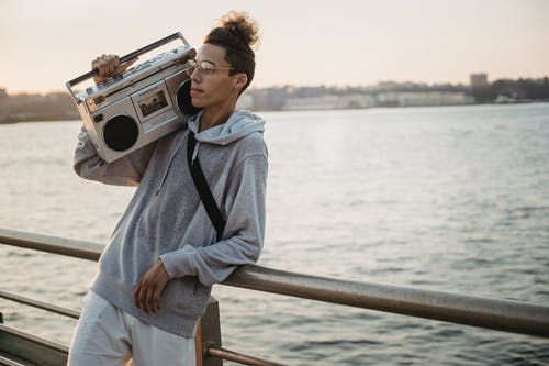 Positive young ethnic male in casual outfit leaning on promenade railing and holding boombox on shoulder while looking away dreamy