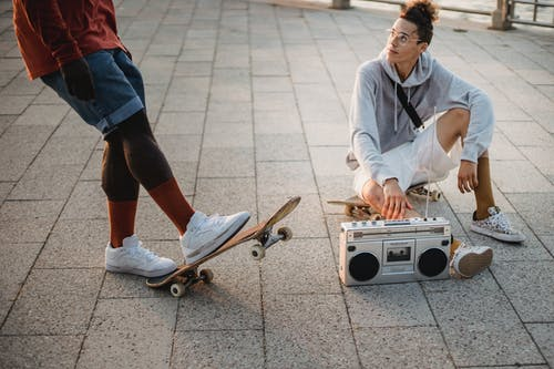 Multiethnic young male skaters wearing casual summer outfits spending time on promenade with skateboards and listening music via tape recorder in evening sun