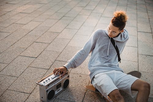 Ethnic male skater sitting on skateboard and switching on boombox