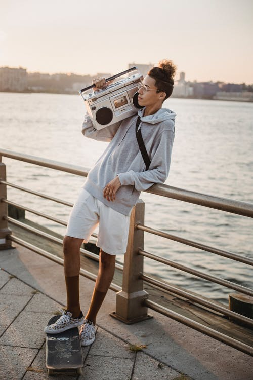 Full length content ethnic male skater standing with boombox on shoulder and leg on skateboard while spending peaceful evening on city embankment and looking away