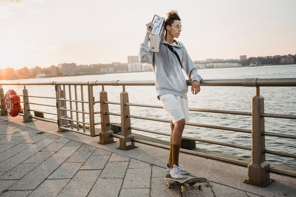 Full length fit ethnic male skater riding skateboard on city embankment with old fashioned tape recorder on shoulder in early evening
