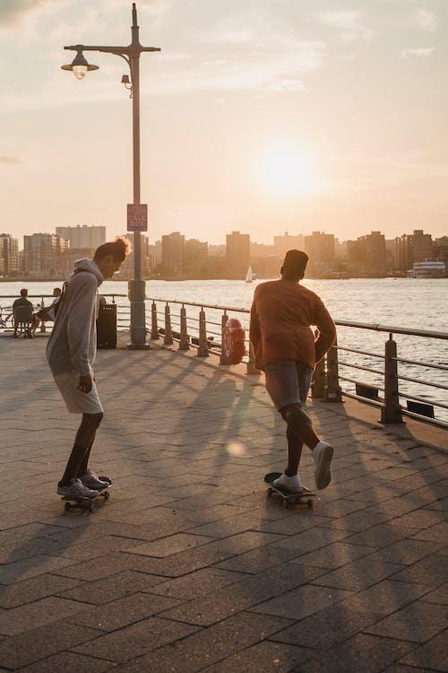 Faceless sporty men skating on embankment at sunset