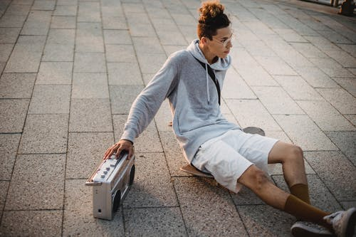 From above young ethnic male skater in casual clothes sitting on skateboard on pavement and listening to music via retro tape recorder in evening