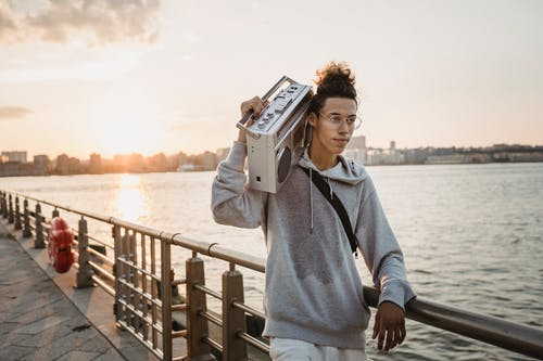 Positive ethnic man carrying boombox on shoulder on embankment