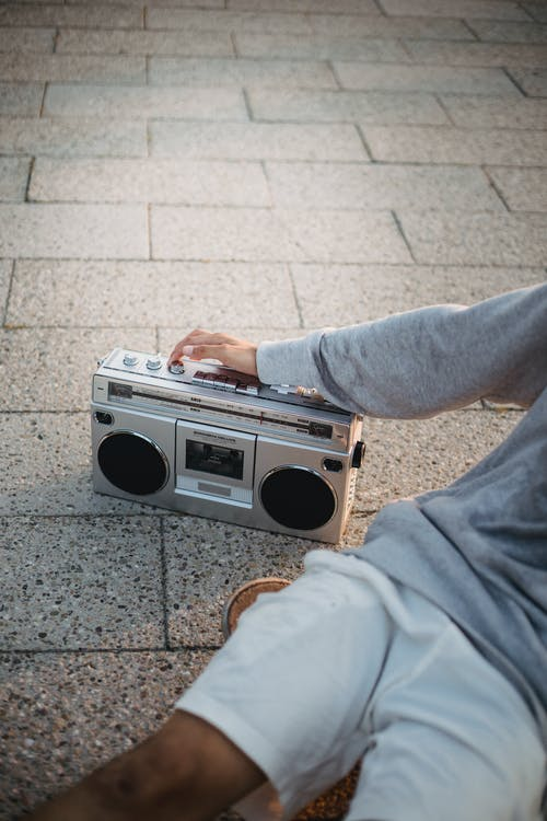Crop anonymous man listening to music with boombox on street