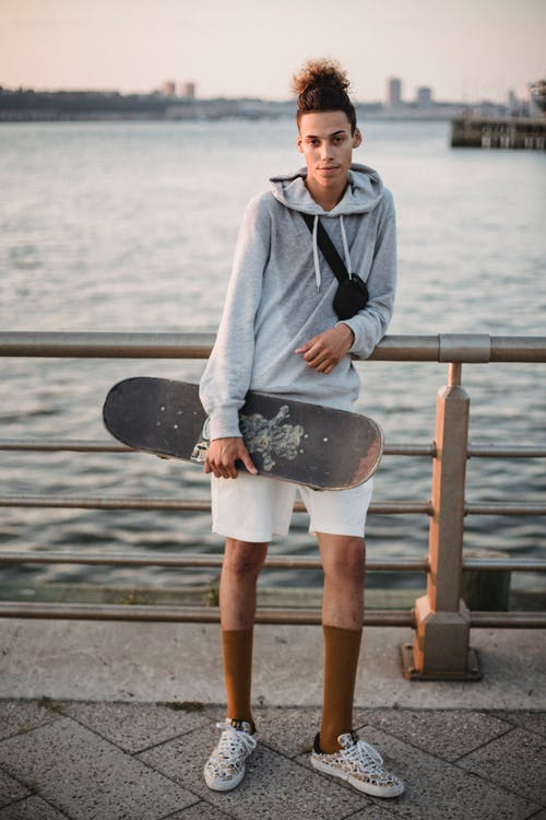 Confident young ethnic man chilling on pier after skateboarding at sundown