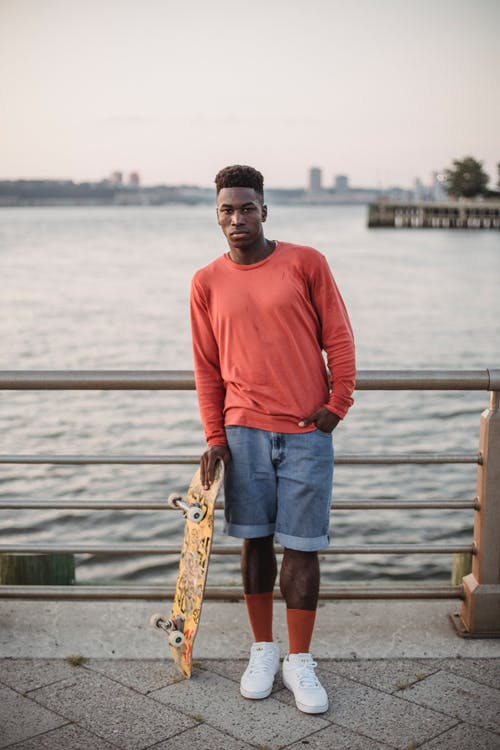 Sporty young black guy chilling on pier after riding skateboard
