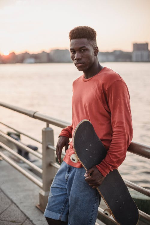 Tired young black guy resting on quay after riding skateboard at sundown
