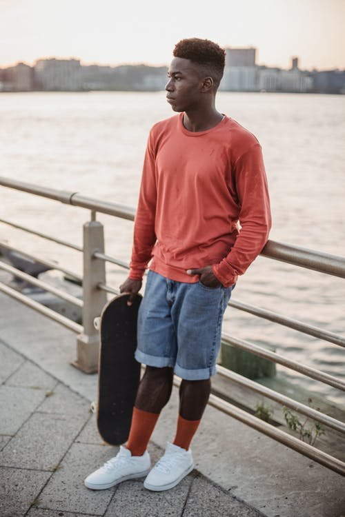 Serious young African American guy with skateboard relaxing on seafront at sundown