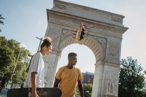 From below of multiethnic male skateboarders standing against aged stone Triumphal Arch in USA