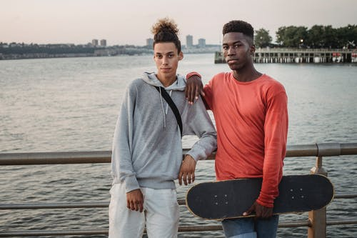 Confident multiethnic friends with skateboard leaning on fence while standing on embankment near wide river during free time together