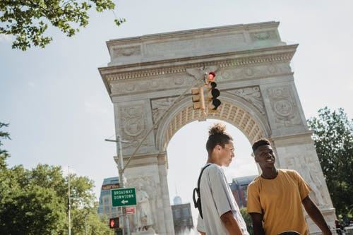 Diverse talking friends standing under traffic light
