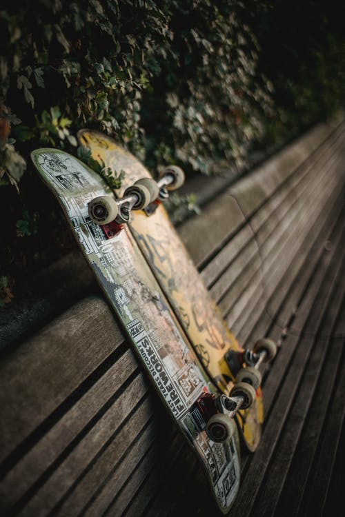 Skateboards placed on wooden bench in green park