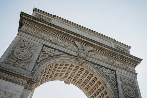 From below of aged architectural monument with ornamental columns and arched passage located in Washington Square Park