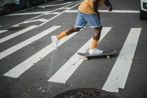 在人行橫道上的黑人男子騎滑板