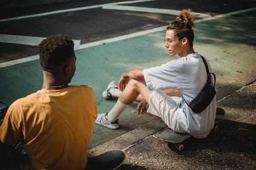 Diverse friends sitting on skateboards in park