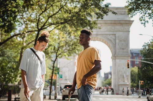Stylish young multiethnic male friends in casual clothes standing on street near Washington Square Arch on sunny day in New York