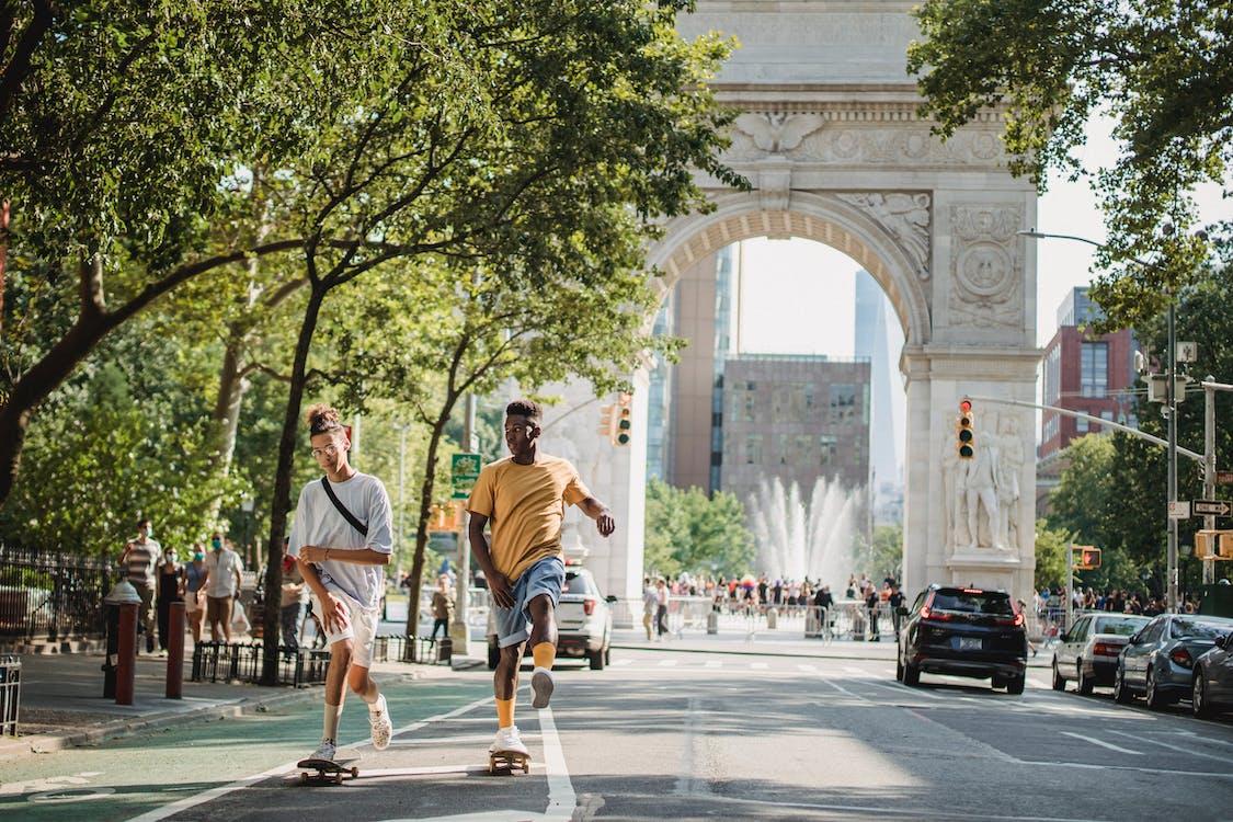 Trendy diverse male teens skateboarding on city street in sunlight