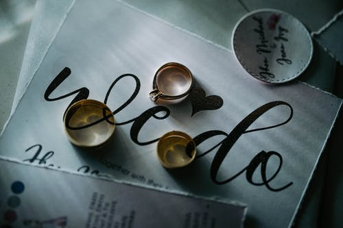 From above of expensive golden rings placed on piece of paper with inscription on table in daylight in room inside